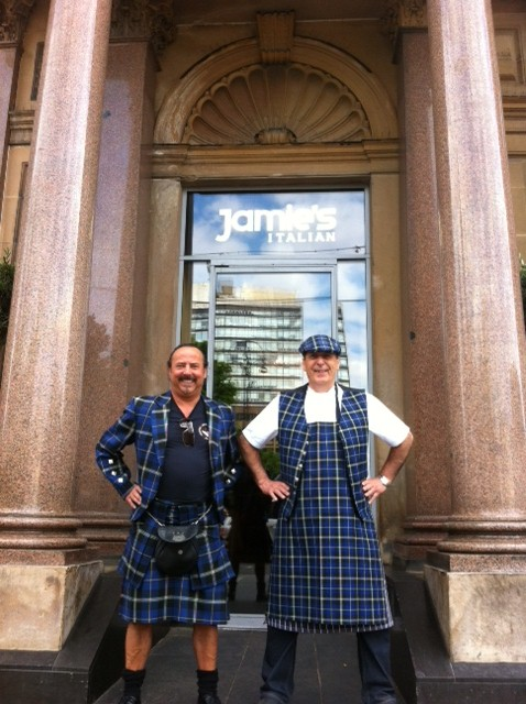 Gennaro Contaldo wearing the Italian National Tartan chef's apron, waistcoat and cap outside Jamie's Italian restaurant in Glasgow with Mike Lem